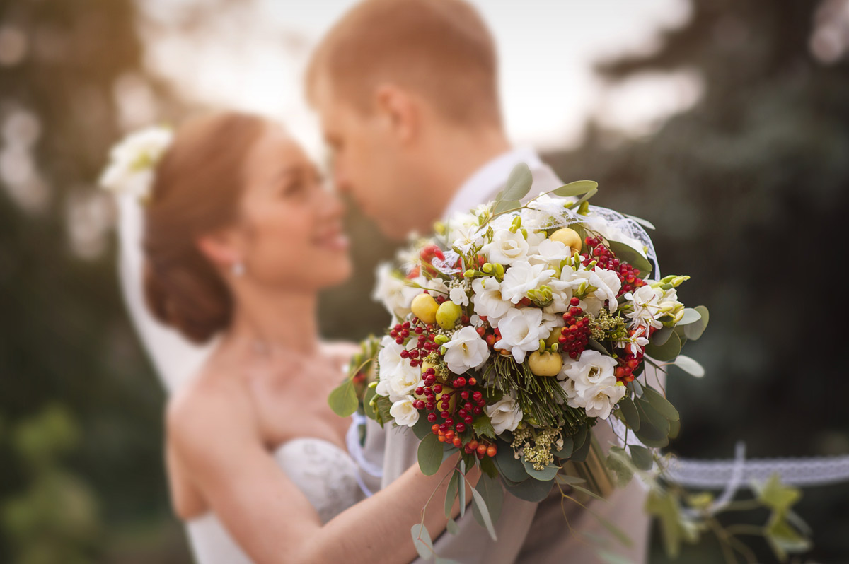 Bride and groom holding wedding flowers